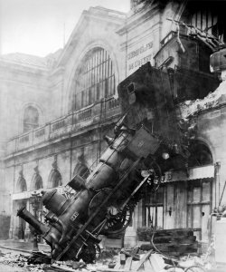 Photo of a train engine that has crashed comletely through the wall of a train station.