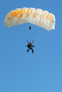 View from below of a person using a parachute