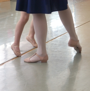 Photo of the feet of an adult showing a young child ballet steps