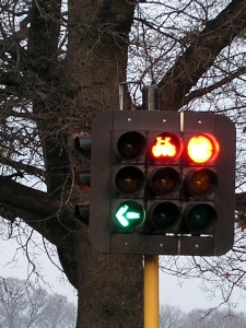 Three traffic lights with the left turn green and the two others red.