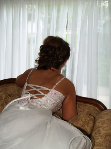 Photo of back of bride as she looks out the window expectantly.