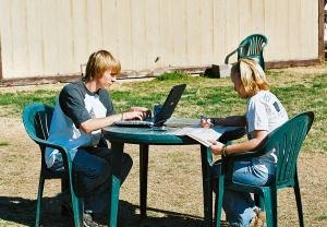 photo of two students, one is on the computer and the other is helping him