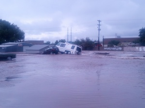 Picture of a car and van in water and on top of something structure.