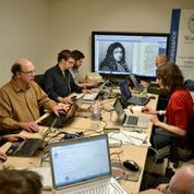 Photo of faculty working together on a computer-mediated class.
