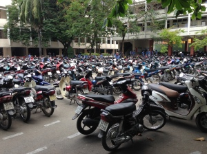 Photo of numerous motorcycles parked at a technical college in Vietnam.
