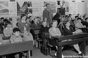 1950's photo of teacher with a film projector in a class of young children.