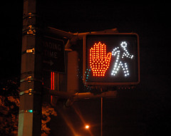 Photo of a crosswalk light that has both the don't walk and walk symbols illuminated.