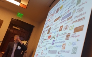 Picture of Sam Greet in front of projection screen with many logos on it.