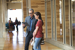 Older male college professor holding a Dell Venue 11 Pro 5000 Series (Model 5130 Midland) tablet computer and showing it to a young female college student, standing in the hallway of a campus building.