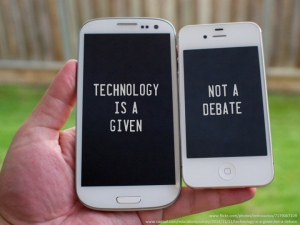 "Hand holding two cell phones. The screen on the first phone reads ""Technology is a given."" The second phone reads ""not a debate."""
