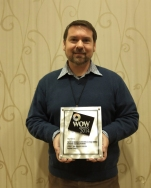 Preston Davis holding a WCET WOW Award.