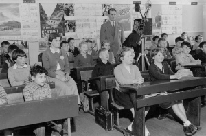 Students in a classroom from the mid -20th century. Teacher has a movie projector.