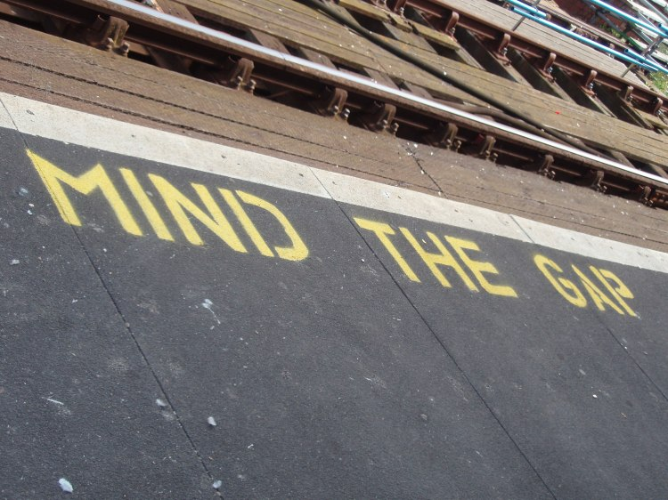 "Railroad tracks with a sign reading ""mind the gap"" to warn passengers boarding the train."