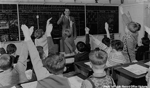 Old picture of a teacher in front of a class of young students. Many of them are raising their hands eager to answer a question.
