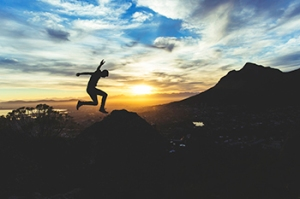 jumping in the mountains at sunset