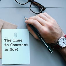 "Picture of a hand with a watch and a pen. The words ""The Time to Comment is Now"" appears on a letter presumably being written by the person in the photo."