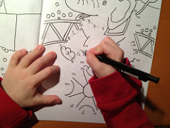 childs hands connecting the dots in coloring book.