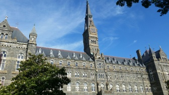 Picture of the stately main building at Georgetown University. It looks slightly like a castle with a tall, narrow clock tower in the middle.