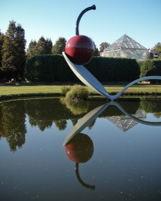 A picture of a very large sculpture of a bent spoon with a cherry in the dish of the spoon. All of this is over a lake at the Minnesota Sculpture Garden.