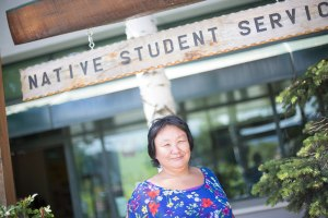 "Eva Greg standing in front of a sign on intentionally weathered wood that reads ""Native Student Services"". She is a Native Alaskan with black hair and a few white specs in it."