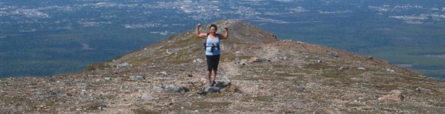Eva raises her hands in triumph at the top of a peak with no trees. Beyond her is the vast vista of Alaska.