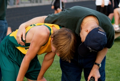 A track coach is leans down next to a young runner who, apparently just completed a race. The coach has his arm around the runner and appears to be consoling him.