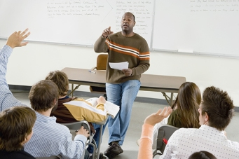 picture of a teacher in the front of a classroom of students seated in rows. The teacher is calling a student who is raising his hand.