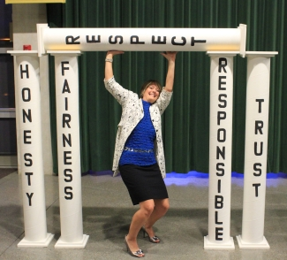 The image of a lady holding up prop-like pillars with words of academic integrity written on them: honesty, fairness, respect, responsible, trust.