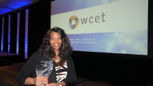 Robbie Melton holding the Richard Jonsen Award in front of a WCET banner