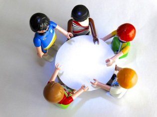 Small, lego figurines in a circle around a mini table.