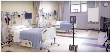 Image of two hospital beds and a tablet attached to wheels (robotics) moving through the room.