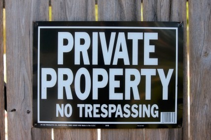 A sign on a fence that states to keep out its private property.