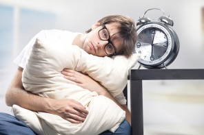 Tired man holding a pillow next to a clock