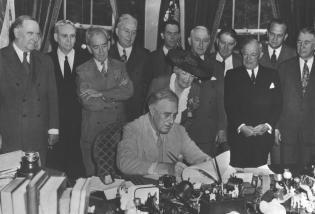 President Roosevelt signing the GI Bill surrounded by others