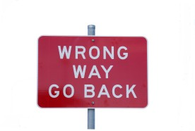 "Street sign reading ""Wrong Way Go Back""."