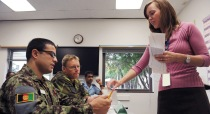instructor hands two military students an assignment