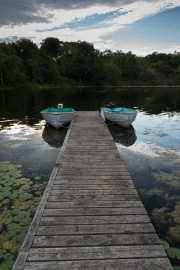 A photo of a lake with two vintage baots, tethered to a long, wooden plank. Behind the boats is lake water, and a bank of the lake with trees.