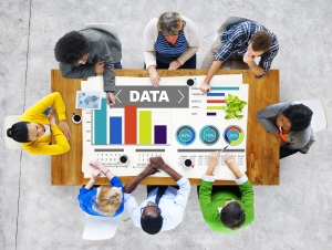 "Several people sitting around a table working on a data project. Poster on table reads ""DATA"" and is surrounded by various charts, graphs."