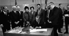 President Lyndon Johnson signing the Higher Ed act surrounded by several witnesses.