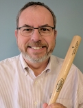 Russ Poulin smiling while holding a small bat