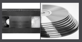 a black and white photo of a vhs tape and cds/dvds