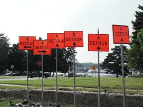 Several detour signs with different arrows facing different directions.