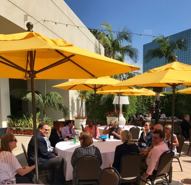 photo of several attendees sitting outside under colorful umbrellas discussing topics.