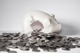 Image of a white piggy bank with the bottom open and coins spilling out