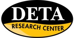 DETA Logo. An oval with black on top and yellow on bottom of logo. At the top the logo reads DETA, underneath it reads Research Center