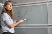 A teacher stands at a glass whiteboard pointing to a graph