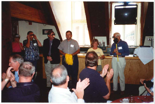 Photo of the graduation ceremony at the now defunct Manager of Distance Education Institute, an early WCET event. From the right: John Witherspoon with the standard (a plunger), Darcy Hardy, Russ Poulin (with the pom poms), Fred Hurst, Ray Lewis, mystery woman in an awesome tiara. Kazoos were used to play