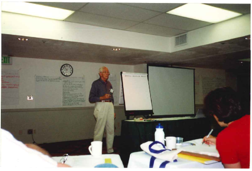 John Witherspoon, the first WCET Steering Committee chair, who was instrumental in setting some of the earlier foundations of WCET. He stands with a microphone in front of a classroom, next to a large notepad and a projector screen.