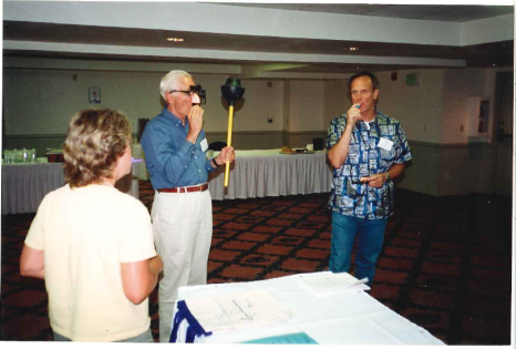 "Darcy, John, and Ray practicing ""pomp and circumstance"" prior to the ceremony above. Three people stand in a room. One is wearing fake glasses, a fake nose, and a mustache and holding a plunger, another is blowing into a kazoo to make music."