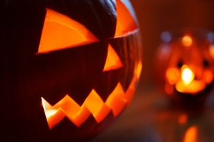 a pumpkin iwth a face carved into it and a candle inside illuminating the face